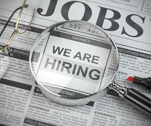 Magnifying glass over We Are Hiring text in a newspaper.